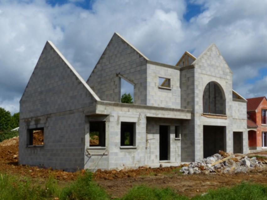 Charpente fermette et mur bloc ponce maison en construction for Construction maison parpaing